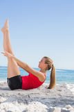 Athletic blonde doing pilates core exercise. On the beach stock photos