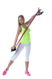 Athletic blonde exercising with stretching trainer Royalty Free Stock Images