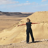 Athletic blonde girl on the edge of cliff. Athletic blonde girl is spreading hands wide on the edge of cliff in the Sahara desert Royalty Free Stock Images