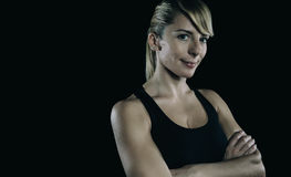 Athletic blonde woman with arms crossed over dark Stock Photos