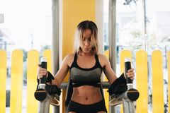 An athletic woman doing exercising abdominals work-out at the parallel bars in a gym. An athletic blonde woman doing exercising abdominals work-out at the royalty free stock photo