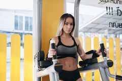 An athletic woman doing exercising abdominals work-out at the parallel bars in a gym. An athletic blonde woman doing exercising abdominals work-out at the stock photography