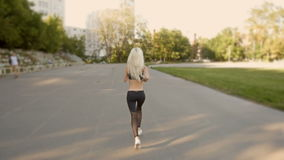 Athletic Blonde Woman Running. Female Runner Jogging. Outdoor Workout.
