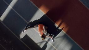 Athletic blonde woman training at indoor stadium. Sportive girl in an orange T-shirt with black pants and light sneakers is doing a stretching exercises at the stock video footage