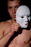 Athletic blonde young man in underwear. Athletic blond young man in white underwear sitting on a chair with white mask Royalty Free Stock Image