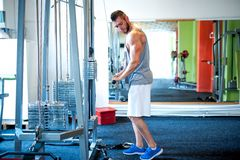 Athletic bodybuilder training at gym, triceps exercises Stock Photos