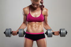 Athletic bodybuilder woman with dumbbells.beautiful blonde girl with muscles. Gym Royalty Free Stock Image
