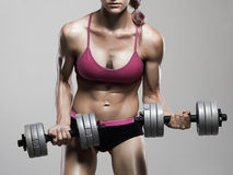Athletic bodybuilder woman with dumbbells.girl with muscles Stock Photo