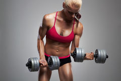 Athletic bodybuilder woman with dumbbells.girl with muscles Stock Photography