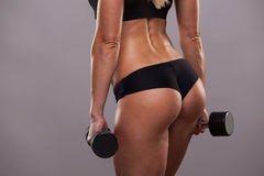 Athletic booty of girl with dumbbells isolated on grey background with copyspace.  Royalty Free Stock Photos