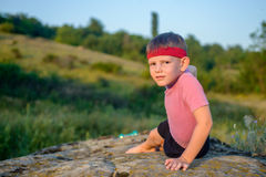 Athletic Boy Doing Side Planking on Top of Boulder Royalty Free Stock Images