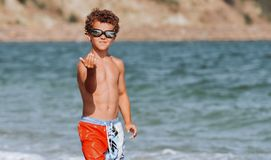 Curly-haired teenager boy in swimming trunks and swimming goggles walks along the seashore under the scorching sun