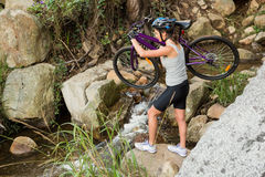Athletic brunette carrying her mountain bike over stream Stock Photos