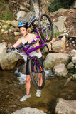 Athletic brunette carrying her mountain bike over stream Stock Images