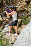 Athletic brunette carrying her mountain bike over stream Royalty Free Stock Photo