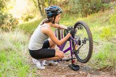Athletic brunette checking her mountain bike Stock Photo