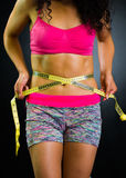 Athletic brunette woman wearing pink top and matching shorts, closeup stomach while measuring abdomen with measure band Stock Images