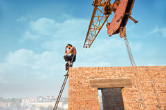 Athletic builder sitting on ladder on high. Athletic builder leaning on brick wall and sitting on ladder on high. Male with bare torso in work wear looking at Royalty Free Stock Photography