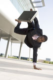 Athletic businessman outside office. Doing a hand stand Royalty Free Stock Photos