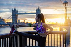 Athletic city woman does her stretches in front of Tower Bridge in London. Athletic city woman does her stretches during sunrise in front of Tower Bridge in royalty free stock photography