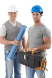 Athletic contractor with engineer guy. Athletic contractor standing holding toolset, engineer guy holding floor plan, wearing hardhat, smiling at camera Royalty Free Stock Photos