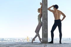 Ballet dancers posing at unfinished building. Athletic couple of ballet dancers lean on the concrete wall on the floor of the unfinished building on the Stock Images