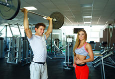 Athletic couple with barbell doing exercises in the gym Royalty Free Stock Photography