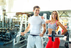 Athletic couple with barbell doing exercises in the gym Royalty Free Stock Images