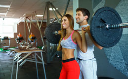 Athletic couple with barbell doing exercises in the gym Stock Photos