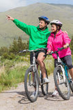 Athletic couple on a bike ride wearing hooded jumpers with man p Stock Images