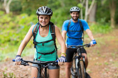 Athletic couple cycling in forest Stock Images
