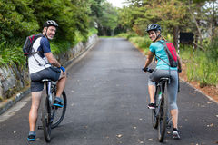Athletic couple cycling on the open road Royalty Free Stock Images