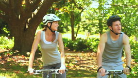 Athletic couple cycling in a wood stock video