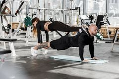Athletic couple doing difficult sport exercise where the girl stands in the plank on a man who stands in the plank in royalty free stock photos