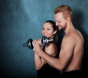 Athletic couple with a dumbells near the wall Stock Photo