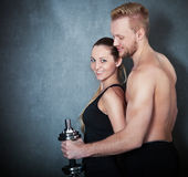 Athletic couple with a dumbells near the wall Stock Photos