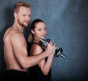 Athletic couple with a dumbells near the wall Stock Images