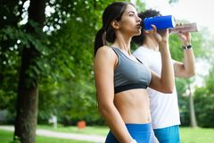 Athletic couple friend drinking water after running royalty free stock photos
