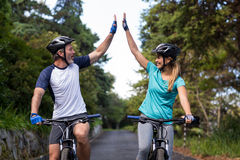 Athletic couple giving high five while riding bicycle on the road Stock Photography
