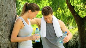 Athletic couple having a drink of water. Couple having a rest and a drink of water after jogging in the park stock footage