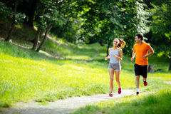 Athletic couple jogging in nature Stock Image