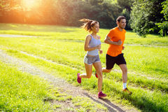 Athletic couple jogging in nature Stock Photos
