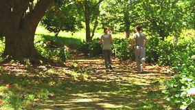 Athletic couple jogging in a wood. Athletic couple running on a path through a wood on a sunny day stock video