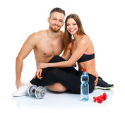 Athletic couple - man and woman after fitness exercise with dumb. Athletic couple - men and women after fitness exercise with dumbbells and bottle of water royalty free stock image