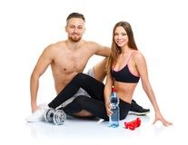 Athletic couple - man and woman after fitness exercise sitting w. Athletic couple - men and women after fitness exercise sitting with dumbbells on the white stock photography