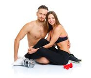 Athletic couple - man and woman after fitness exercise sitting w. Athletic couple - men and women after fitness exercise sitting with dumbbells on the white stock photo