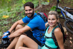 Athletic couple relaxing in forest. Portrait of smiling athletic couple relaxing in forest Royalty Free Stock Photo