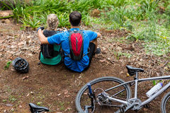 Athletic couple relaxing in forest. Rear view of athletic couple relaxing in forest Royalty Free Stock Photos
