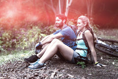 Athletic couple relaxing in forest. Smiling athletic couple relaxing in forest Stock Photo