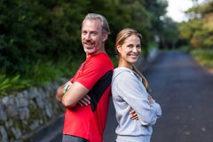 Athletic couple standing back to back on the open road Royalty Free Stock Photo